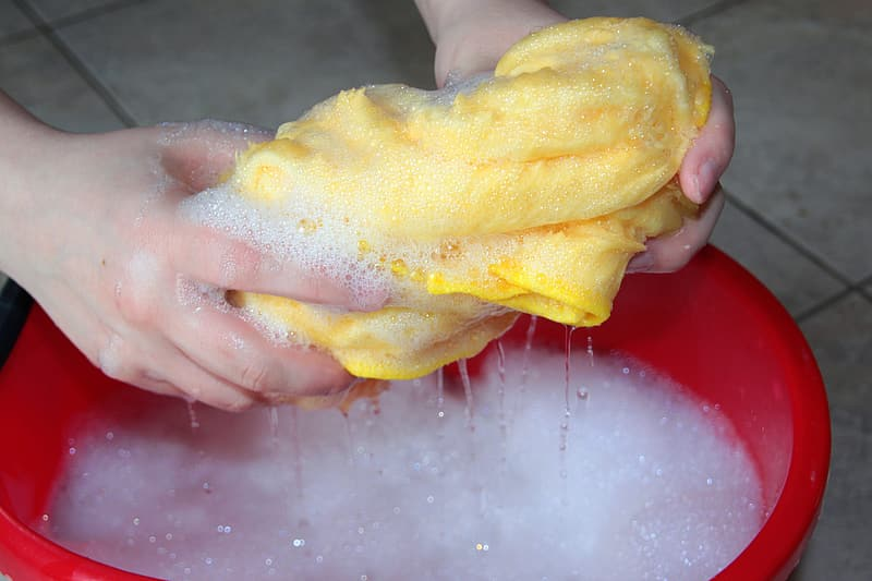 Person washing yellow shirt on red plastic basin