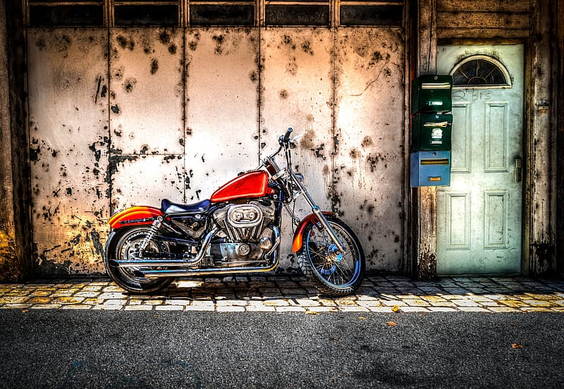 Parked red motorcycle outside white metal walled building with green door
