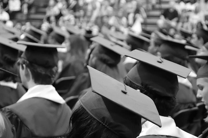 Grayscale photo of student wearing academic gowns