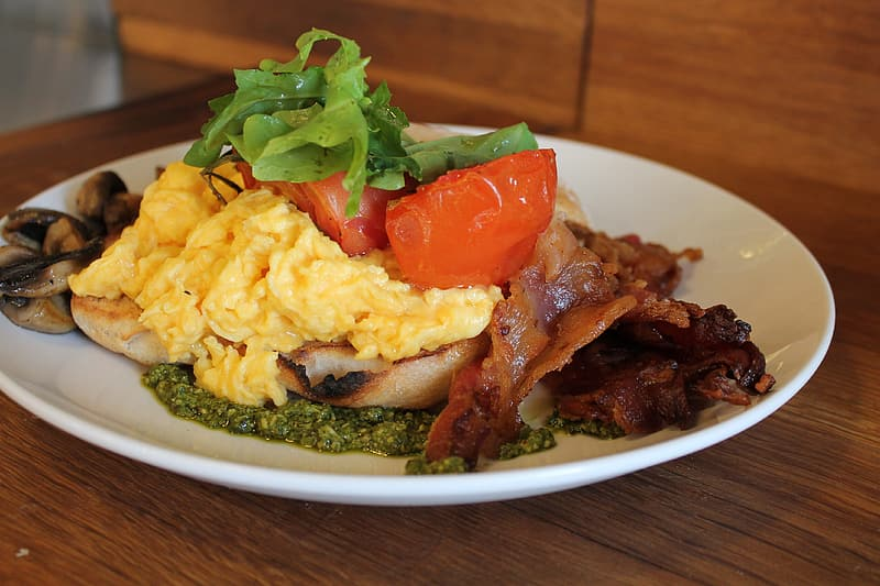 Fried bacon strip and scrambled egg served in plate