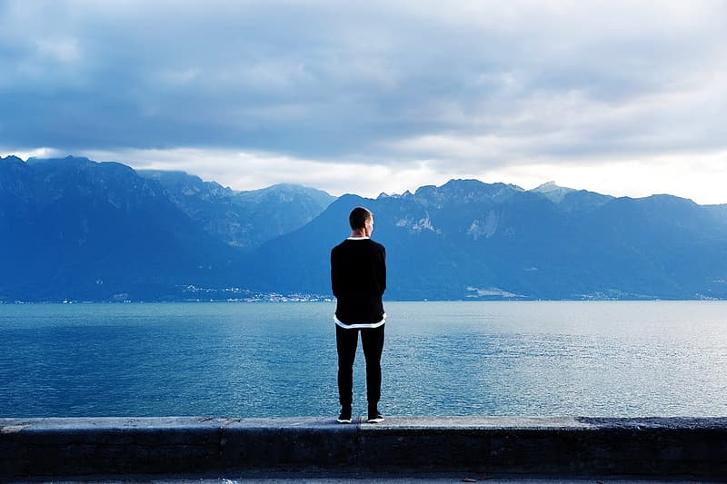 Man in black jacket standing on concrete pavement near body of water during daytime