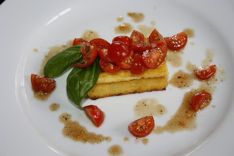 Brown bread with red tomato on white ceramic plate