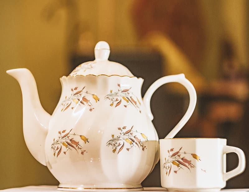 White and brown ceramic teapot beside teacup