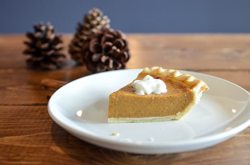 Pie on white plate and pine cones closeup photo