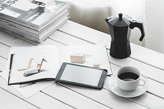 White ceramic teacup near black smartphone on table