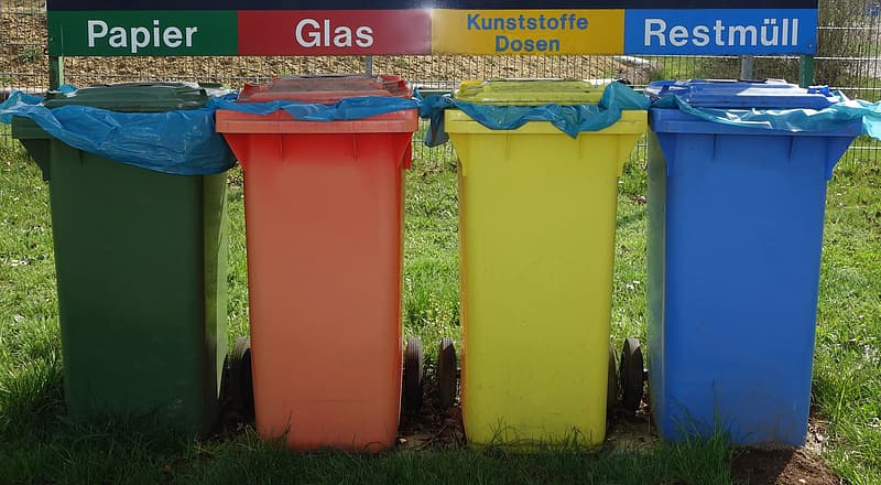 Four assorted-color plastic organized garbage bins