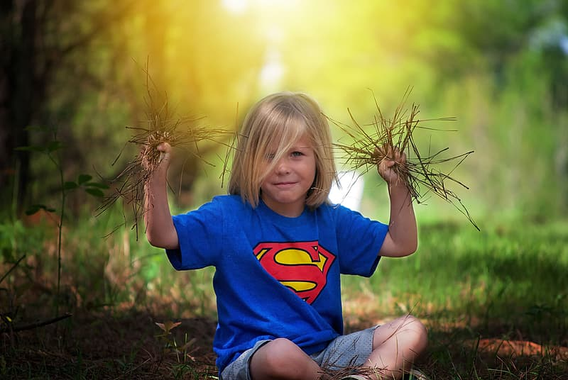 Shallow focus photography of boy in blue Superman shirt