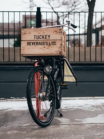 Brown wooden box on top of bicycle parked near black railings