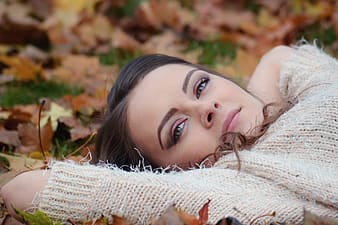 Woman portrait wearing sweater laying in leaves