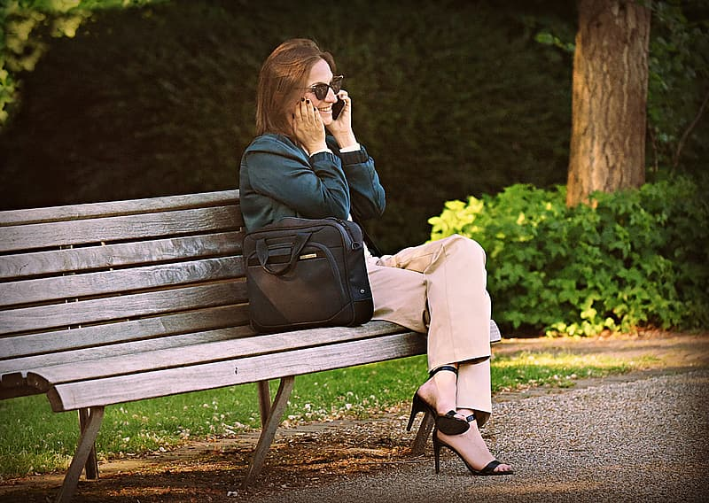 Woman in black leather jacket and beige pants sitting on brown wooden bench during daytime