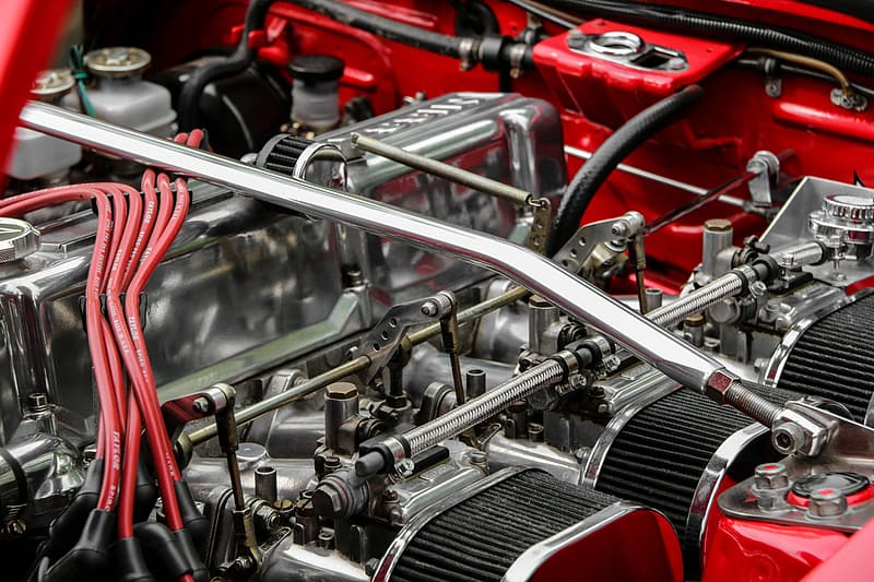 Gray and red vehicle engine bay close-up photo