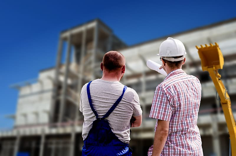 Two men standing in front of concrete structure during daytime