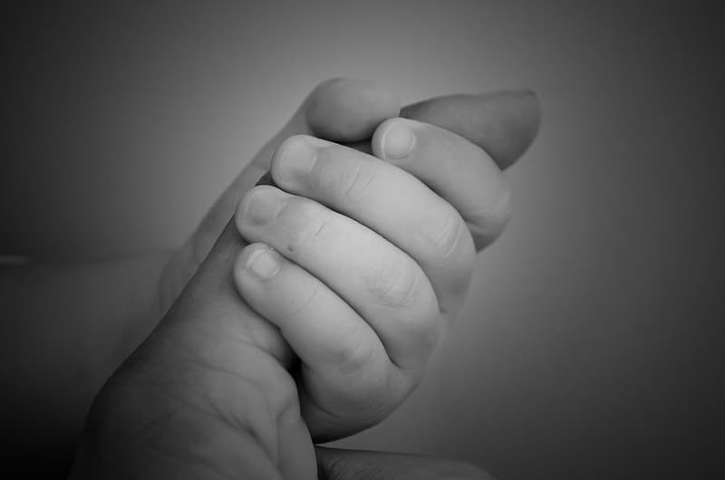 Grayscale photo of baby holding index finger