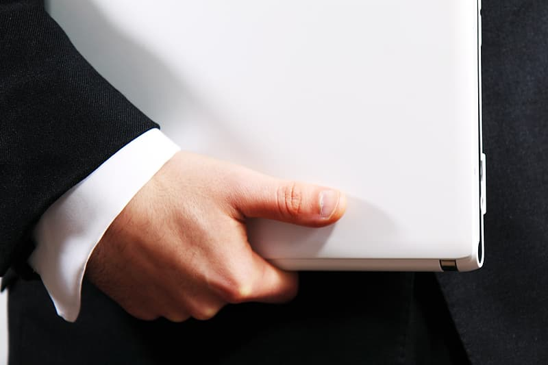 Person holding white laptop computer