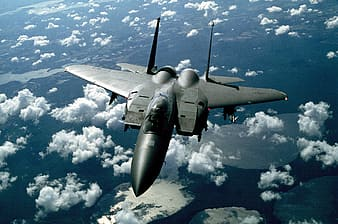 Gray jet fighter above clouds during daytime