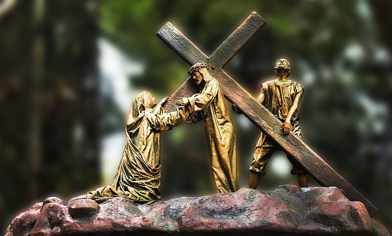 Gold statue of man holding cross