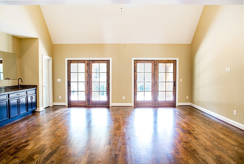Beige painted wall with two brown wooden-framed 8-lite doors on brown wooden parquet