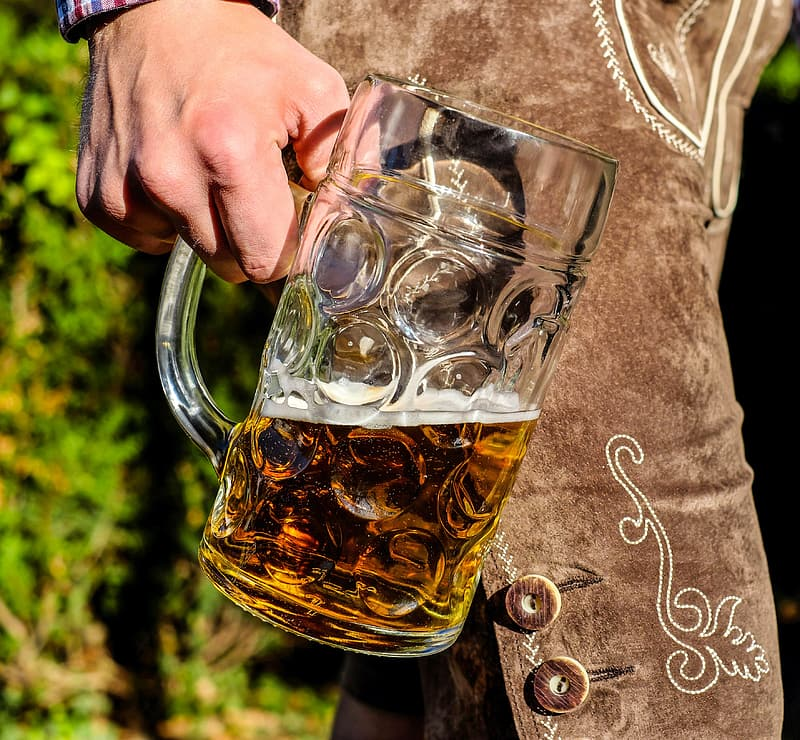 Person holding clear glass beer mug