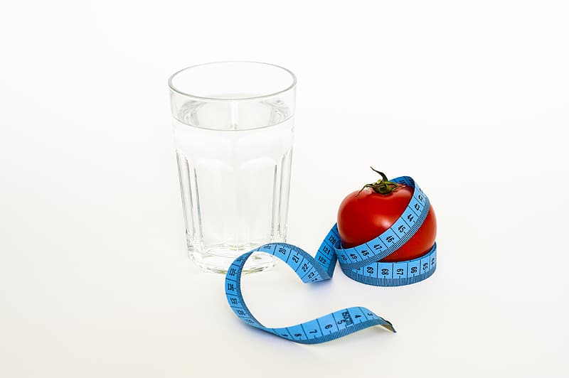 Clear drinking glass beside red tomato
