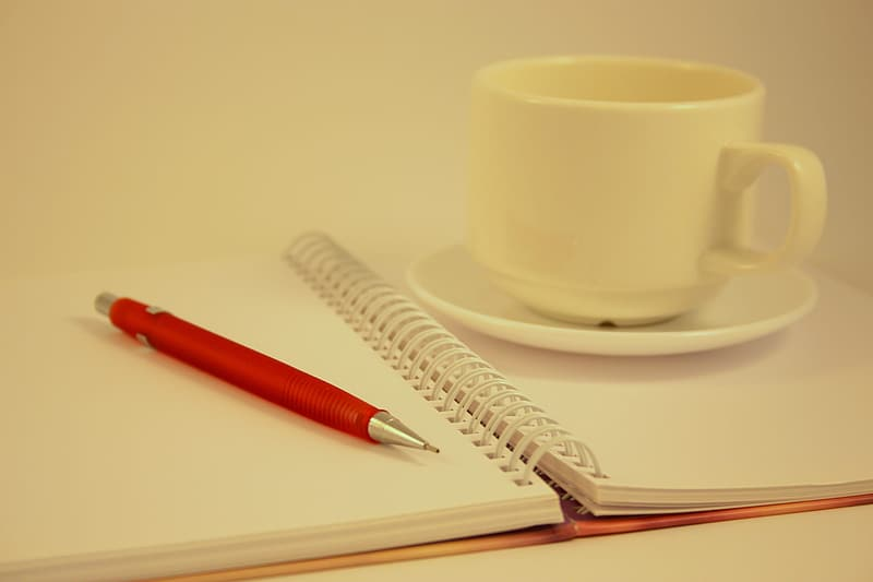 White ceramic teacup on saucer on top of opened notebook beside red mechanical pencil