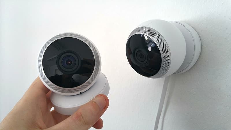 Person holding white security camera beside wall-mounted security camera