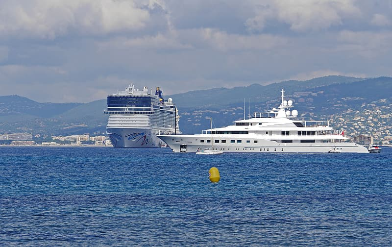 White yacht moving on calm body of water near cruise ship during daytime