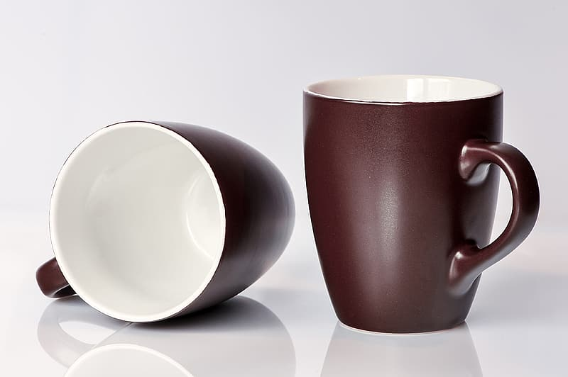 Two black-and-white ceramic mugs on white surface
