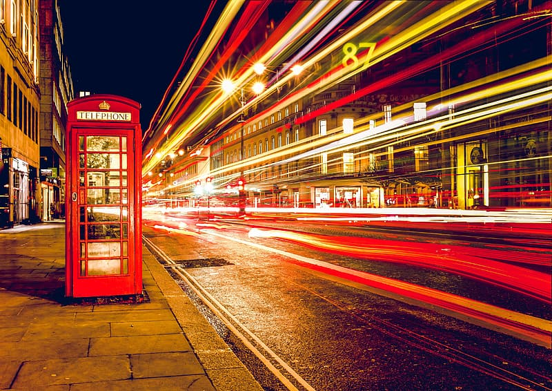 Time-lapse photo of vehicle creating light streaks near telephone booth