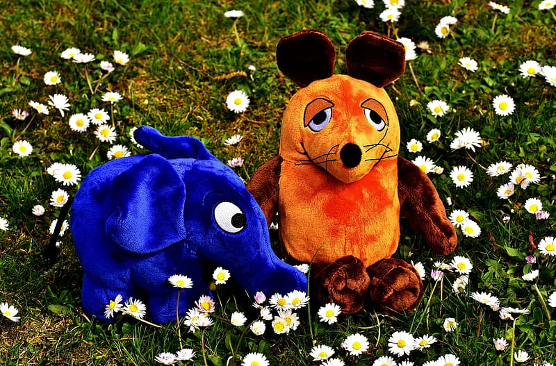 Two blue elephant and brown and orange mouse plush toys on white flower field at daytime