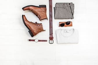 Black sunglasses and brown leather boots on white textile