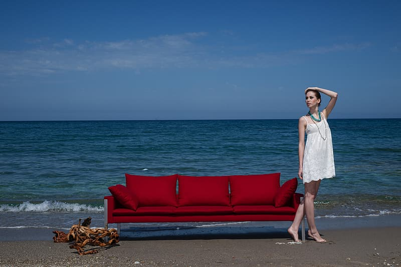 Woman in white spaghetti strap mini dress standing beside red couch