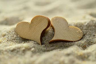 Two heart shape wooden decoration on sand