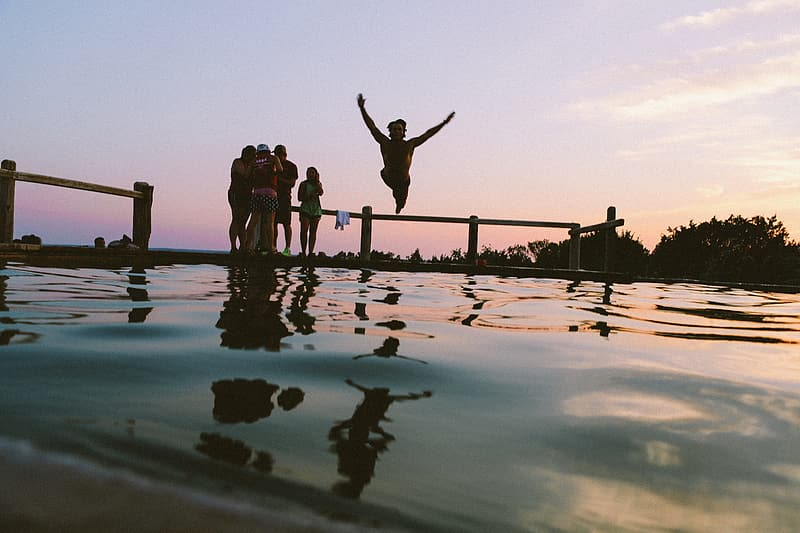 Silhouette of people jumping on water during sunset