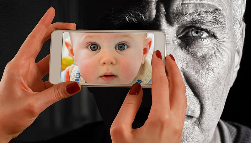 Person holding white smartphone with baby's face wallpaper