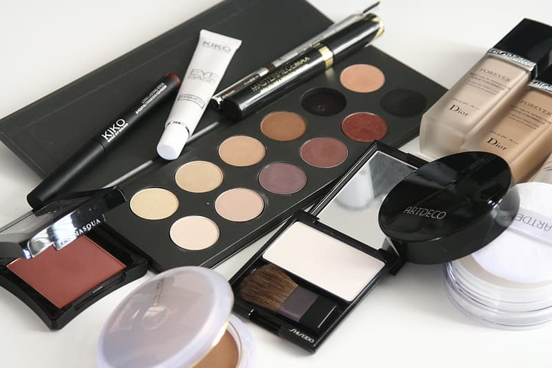 Assorted-color makeup palettes on white surface