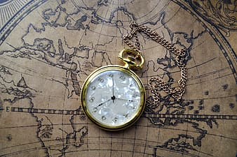 Round gold-colored framed analog pocket watch on brown map