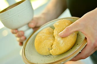 Person holding saucer with baked bread