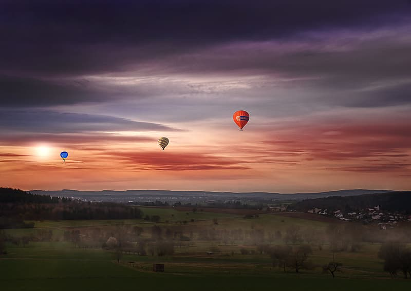 Blue, yellow, and orange hot air balloons flying over green grass field during sunset