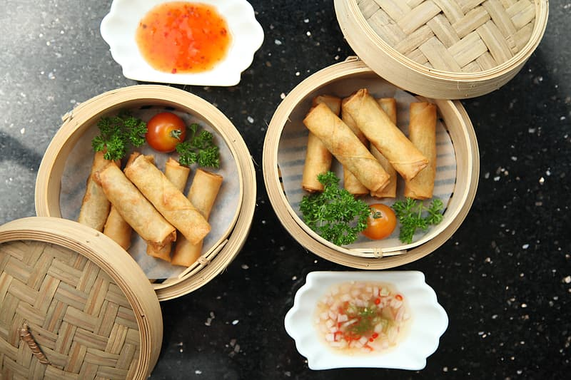 Two round brown container with spring rolls