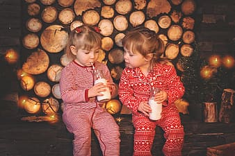 Two girls wearing footie pajamas sipping drink