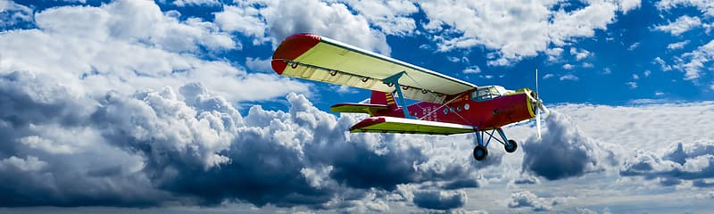 Yellow and red plane flying under white clouds