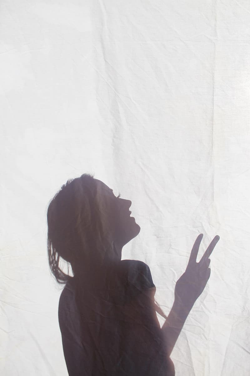 Silhouette of woman doing peace sign on white textile