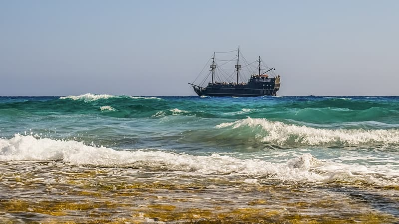 Brown sail ship anchored off shore