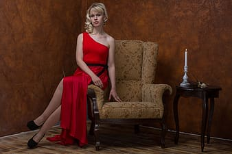 Woman in red spaghetti strap dress sitting on brown sofa chair