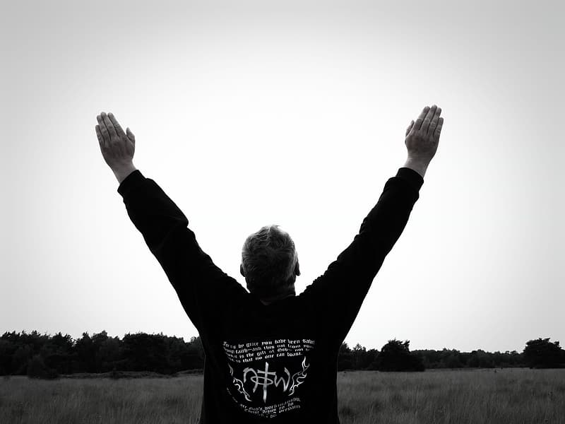 Grayscale photo of man raising his arms