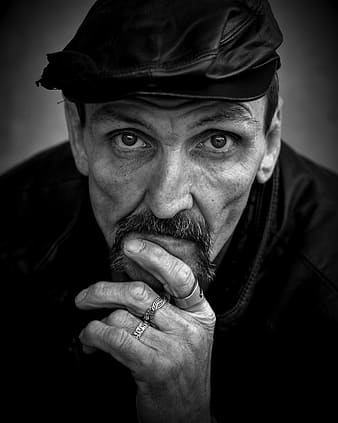 Grayscale photo of man with leather flat cap