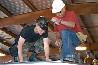 Two men fixing roof