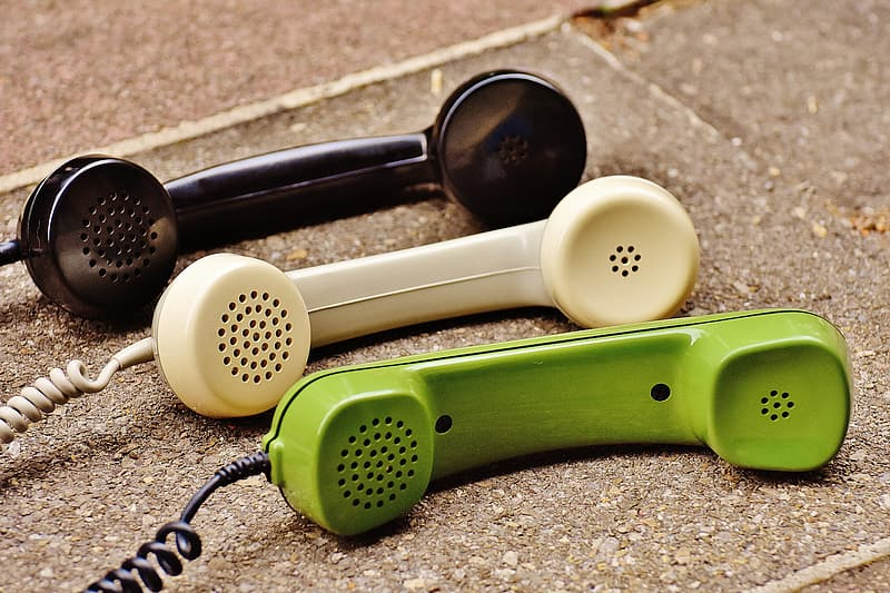 Green, white, and black telephones