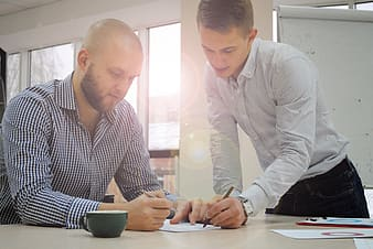 Two men writing on white paper inside white painted room