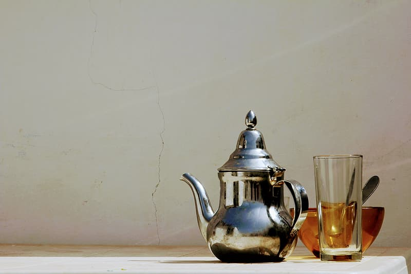 Gray stainless steel kettle near clear drinking glass